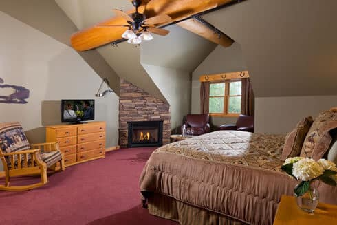 Spacious bedroom with wood beams, fireplace and sitting area below a large window