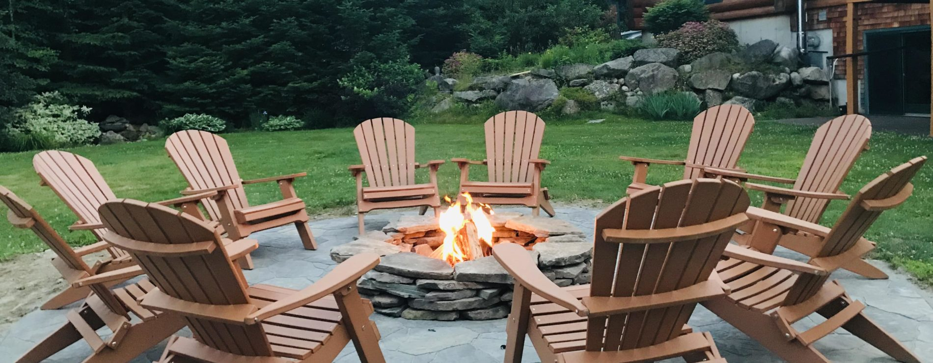 Ten brown Adirondack chairs circling a fire pit on an outdoor stone patio