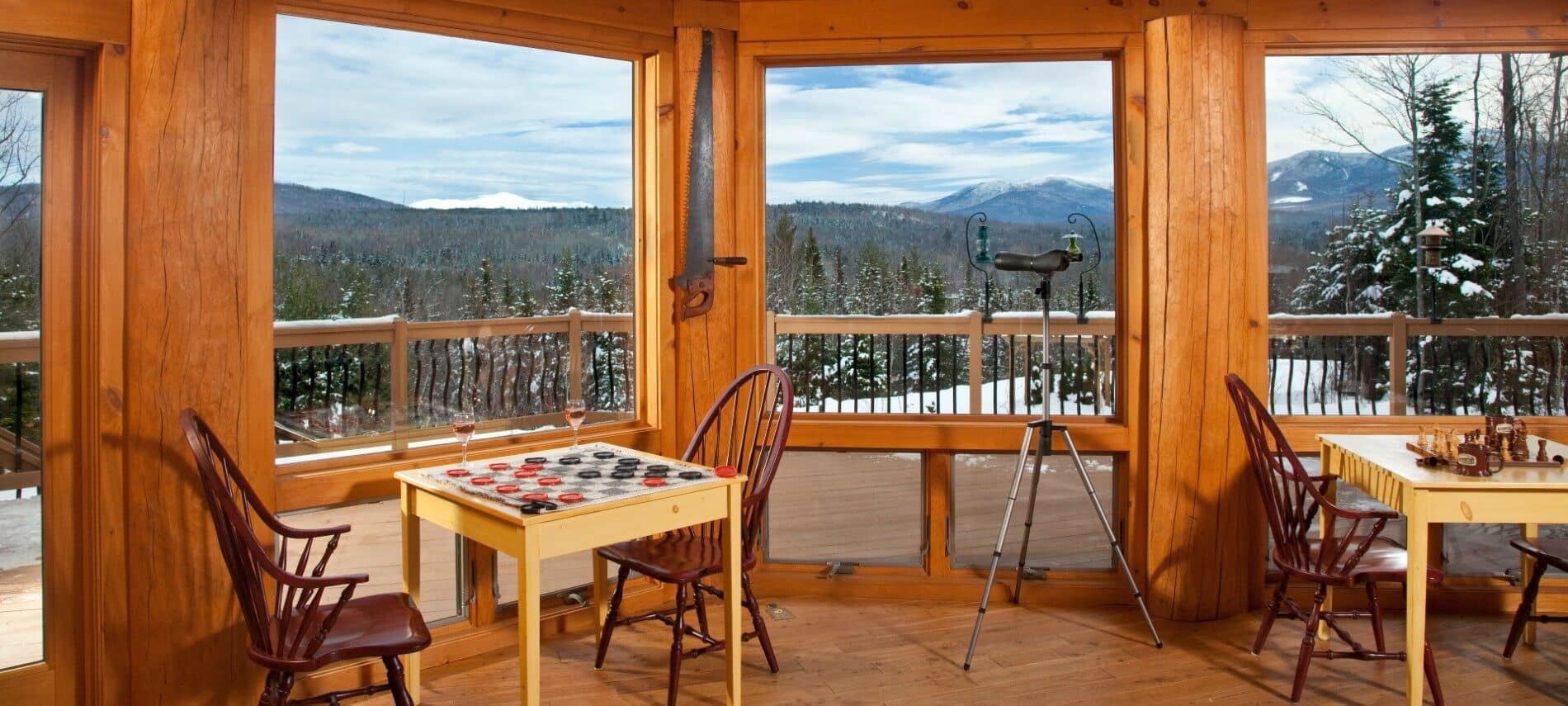 Corner of a log cabin home with two game tables and chairs in front of large picture windows overlooking mountains