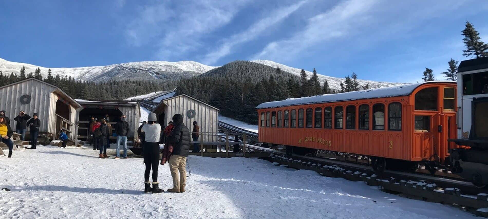 Bright orange cog railway car sitting on a track at the bottom of a mountain with people standing around