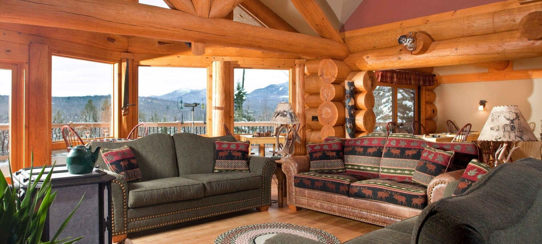 Living area of a log cabin home with couches, table and chairs and large picture windows