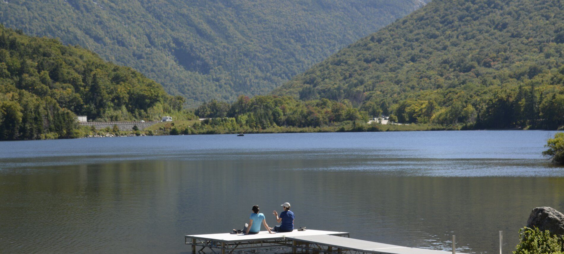 Two people sitting at the edge of a dock in front of a large lake at the bottom of a mountain range