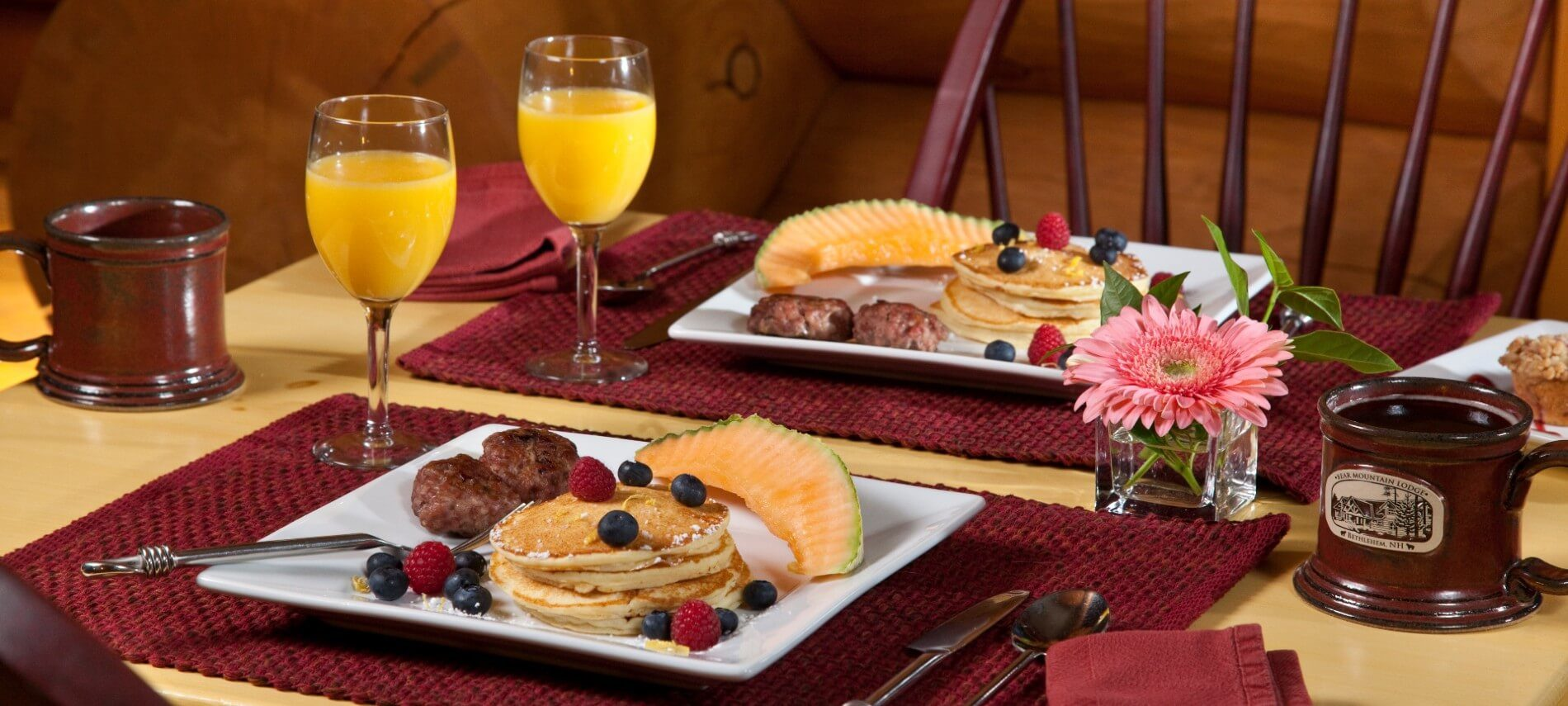 Breakfast table set for two with white plates holding pancakes, fruit and sausage