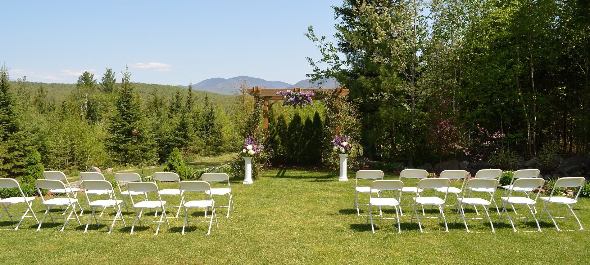 White chairs set up on a lawn next to a pergola arch for an outdoor wedding