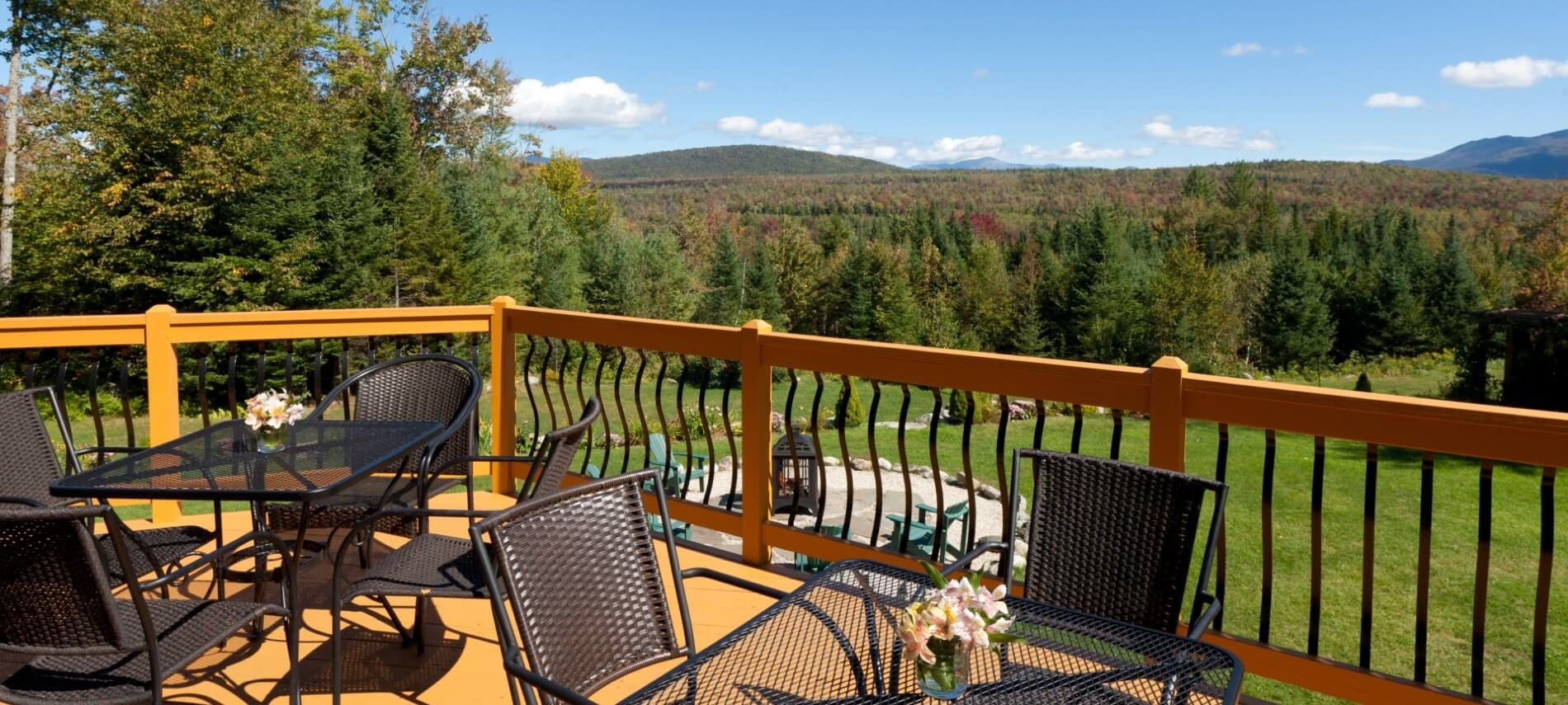 Outdoor deck with wood and iron railings and patio furniture overlooking a lawn and mountain range