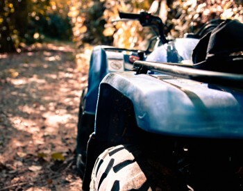 A black ATV sitting on a trail with surrounded by trees in sunlight