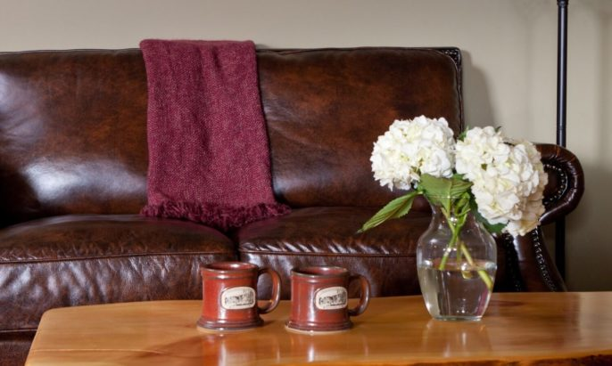 Plush leather loveseat with burgundy throw blanket and coffee table holding two ceramic mugs and a vase with white hydrangeas