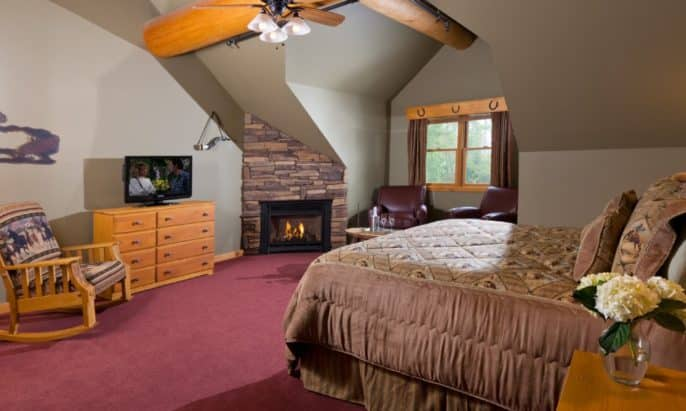 Large bedroom with a king-size iron bed, stone gas fireplace, leather sitting chairs by a window and a wooden rocking chair