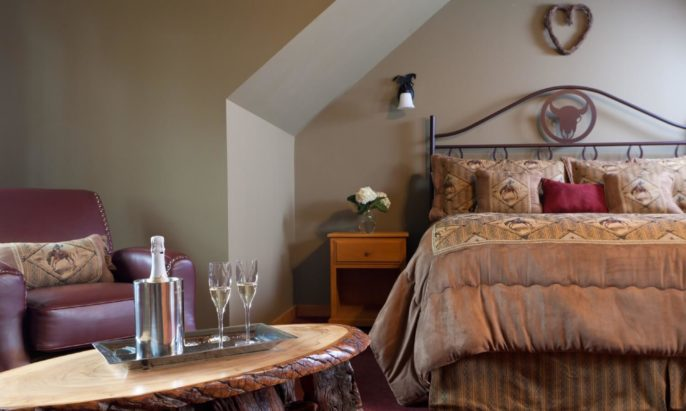 King-size iron bed in a bedroom with leather chair and wood coffee table holding champagne bottle and two flutes