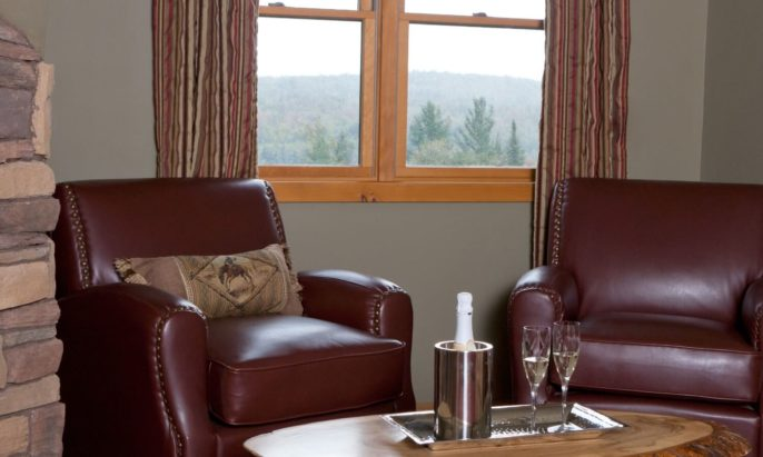 Two plush leather sitting chairs and coffee table holding champagne bottle and two glasses below a bright window overlooking a wooded area