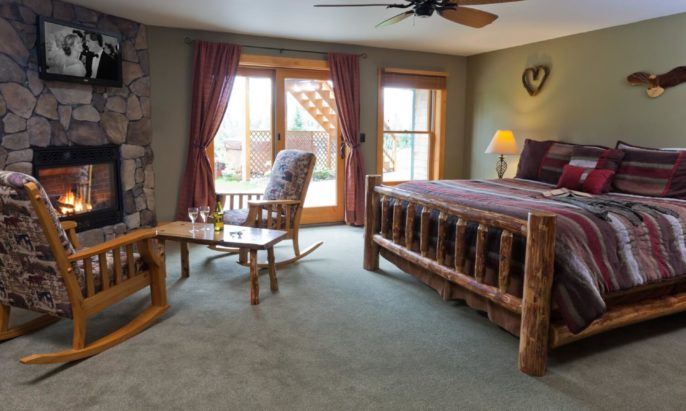 King-size log bed in room with floor to ceiling stone gas fireplace, wooden rocker chairs and access to patio