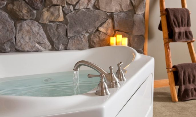 In-room 2-person Jacuzzi tub full of water with three lit candles