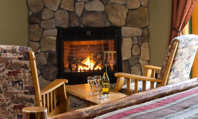 Two wood chairs and side table holding wine bottle and two glasses in front of lit stone gas fireplace