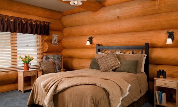 Log cabin bedroom with queen size bed, side table and chair with table by large window