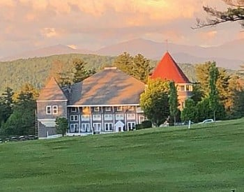 Large golf course clubhouse by an expansive green lawn with mountain range in background