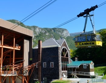 Large gondola complex at the bottom of a mountain range with blue skies above