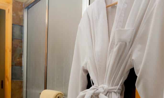 Bathroom with glass shower doors and one white luxurious robe hanging on a wooden hanger