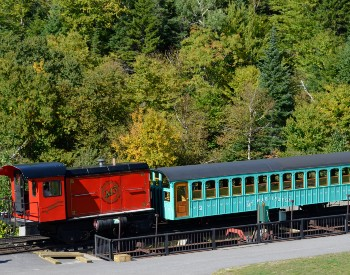 Blue cog railway car sitting on a track at the bottom of a tree covered mountain range