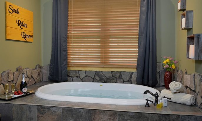Fabulous stone spa room with Jacuzzi tub, tray with champagne and strawberries and rolled towels