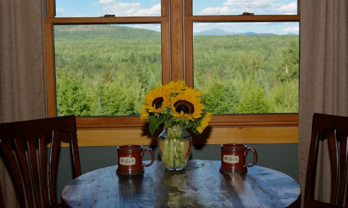 Round wooden table for two holding mugs and vase of sunflowers overlooking a wooded valley