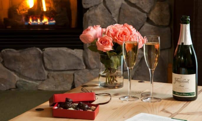 Coffee table holding champagne bottle and two flutes, vase of pink roses and box of chocolates in front of a stone gas fireplace