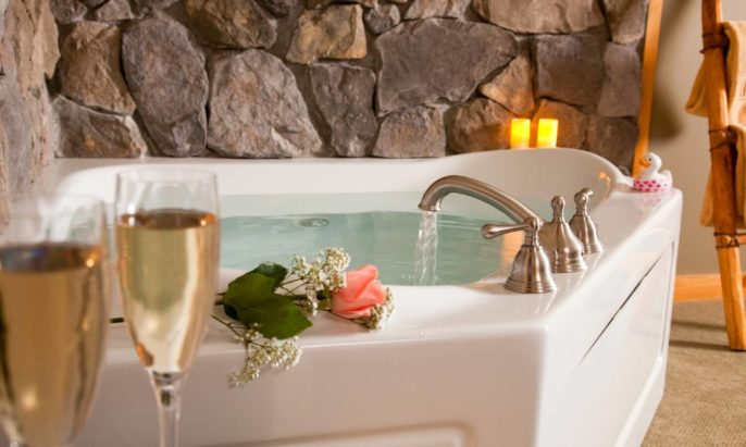 In room 2-person Jacuzzi tub surrounded by stone with single pink rose, lit candles, and two champagne flutes
