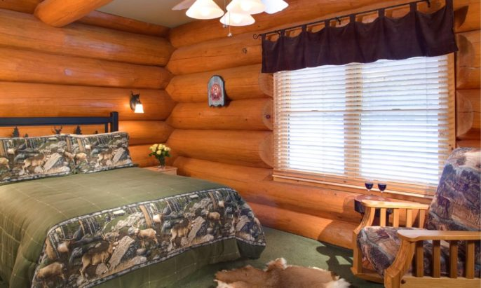 Cozy log cabin bedroom with queen bed in a green quilt, wood rocker chair and large bright window