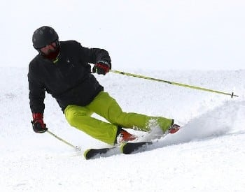 A skier with a black jacket and green pants coming down a powdery ski hill