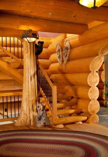 Stairway of a log cabin home with tree trunk feature and large woven rug