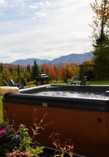 Outdoor hot tub with lawn, firepit, trees and mountain range in the background