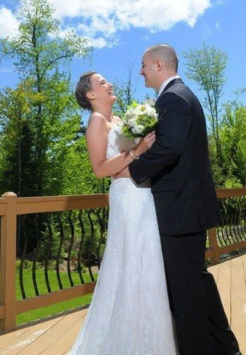 A bride and groom standing on an outdoor deck surrounded by trees and blue skies