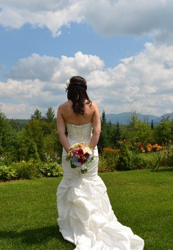 A bride holding a bouquet behind her back and facing an expansive forest and mountain range