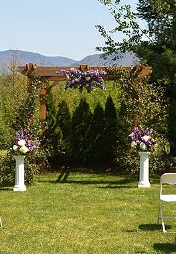 Tall wood pergola arch covered in greenery and flowers with flower bouquets atop two short white columns