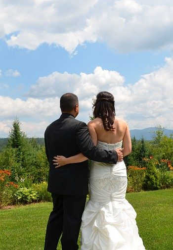 A bride and groom, arm in arm, standing on a lawn looking towards trees and mountain range